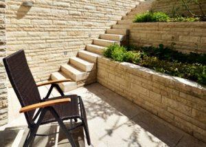 Blick auf eine Naturstein Bossenmauer und Blockstufen aus beigem Travertin Bauhaus von TRACO