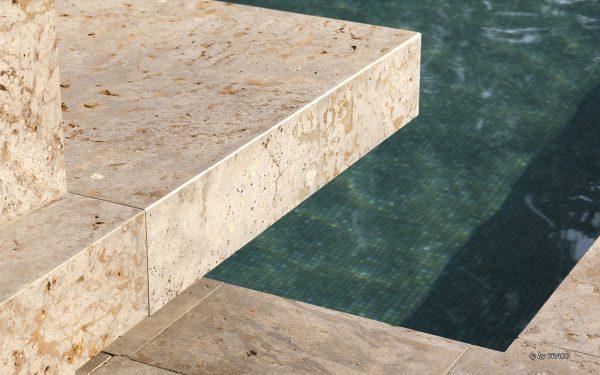 Nahaufnahme Poolumrandung aus hellem Naturstein von TRACO