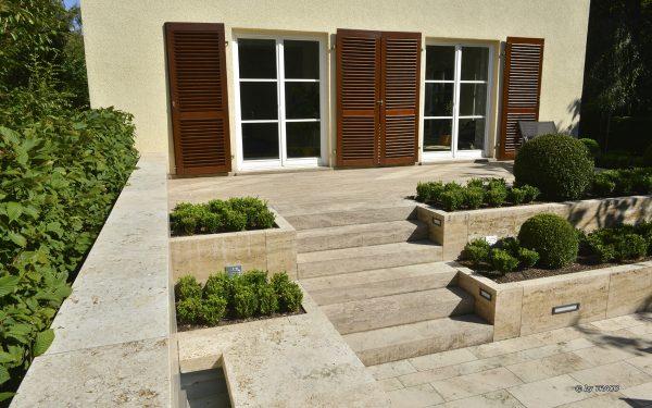 Gartengestaltung mit Bodenplatten, Randeinfassung mit Wasserspiel und Blockstufen aus beigem Travertin Thüringen von TRACO