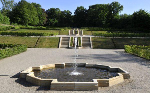 Ansicht des Brunnens aus gelb/weißen Seeberger Sandstein von TRACO mit Wasserlauf im Barockgarten Schloss Gottorf in Schleswig