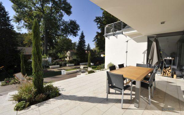 Terrasse mit Bodenplatten aus hellem Naturstein von TRACO