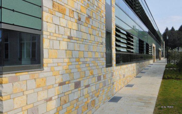 Fassade aus verschiedenfarbigen Natursteinen von TRACO