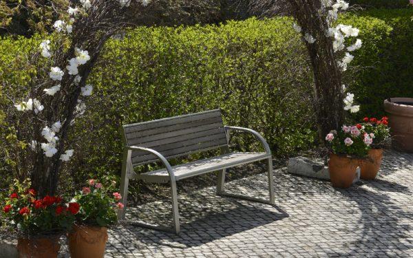 Pflaster aus Naturstein von TRACO als Gartenweg vor Hecke