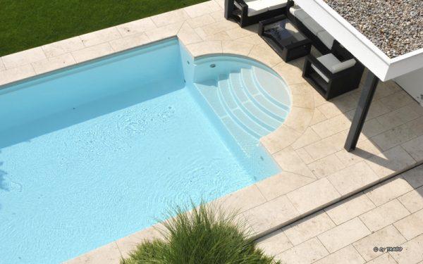 Terrassenbelag und Pool-Einfassung aus beigem Travertin Bauhaus von TRACO