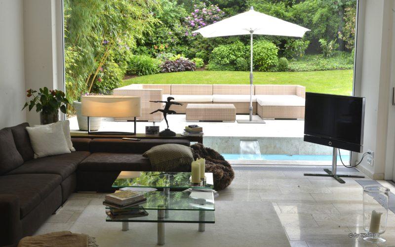 Blick in ein Wohnzimmer und durch ein großes Fenster auf eine Terrasse. Natursteinboden innen sowie Terrassenbelag aus beigen Travertin Bauhaus von TRACO