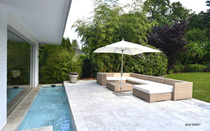 Villa mit Pooleinfassung und Terrassenplatten aus beigen Travertin Bauhaus von TRACO