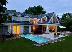 Nachtaufnahme einer Villa mit Pooleinfassung und Terrassenplatten beigen Travertin Bauhaus von TRACO