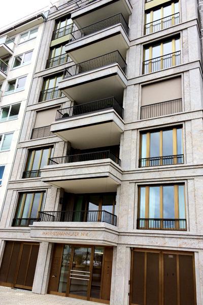 Ansicht auf ein Wohnhaus am Mannesmannufer in Düsseldorf mit dreidimensionaler Natursteinfassade aus grauem Mooser Muschelkalk von TRACO