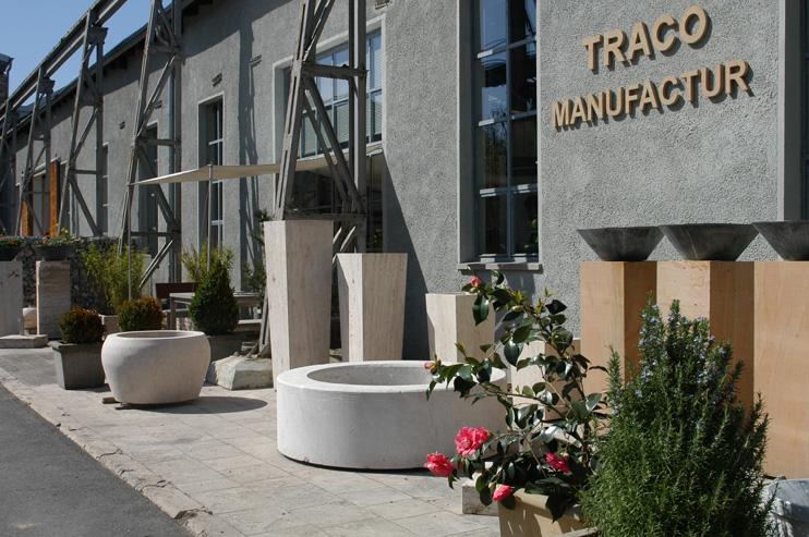 Außenansicht der TRACO Manufactur Ausstellung mit Pflanztrögen im Vordergrund