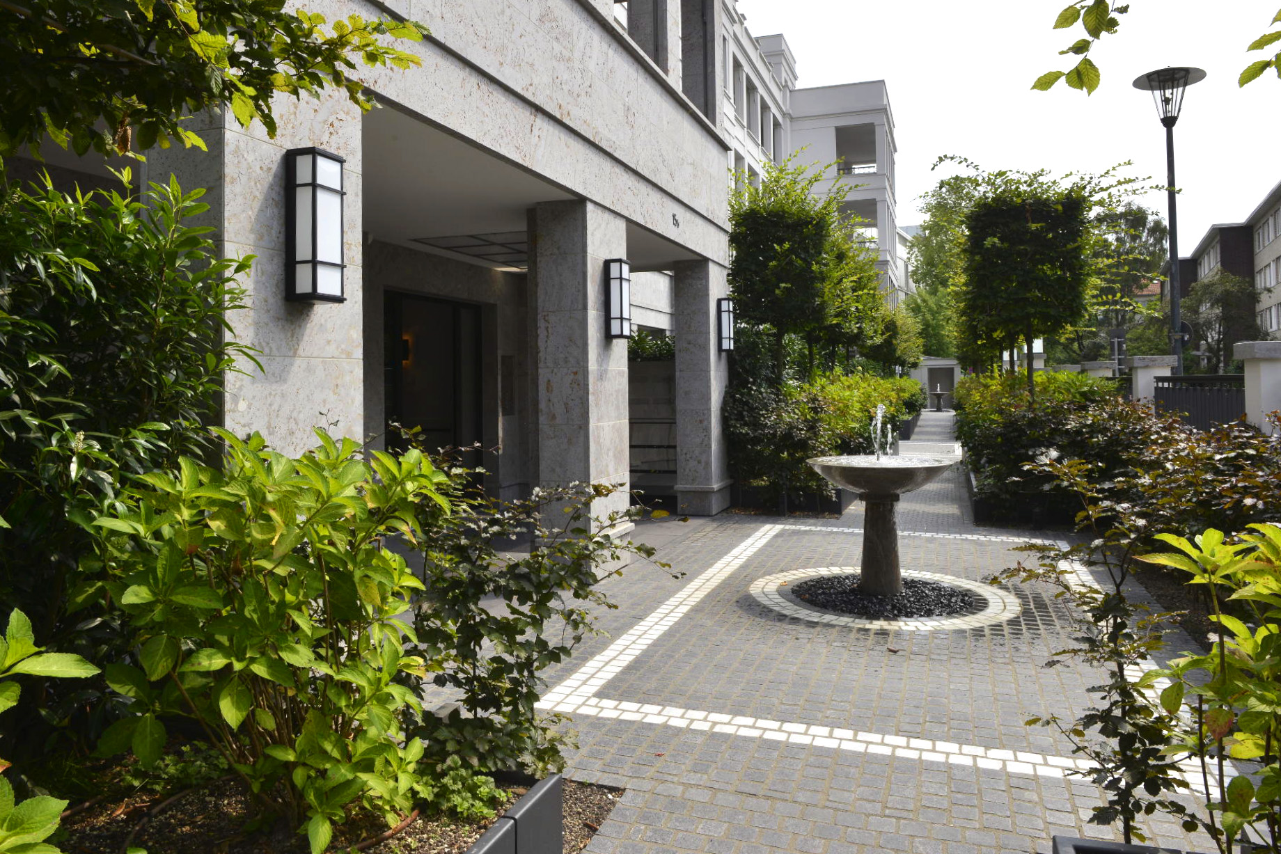 Luxuswohnanlage in Düsseldorf mit Brunnen im Vorhof und Fassadenplatten sowie Massivarbeiten aus grauem Mooser Muschelkalk von TRACO