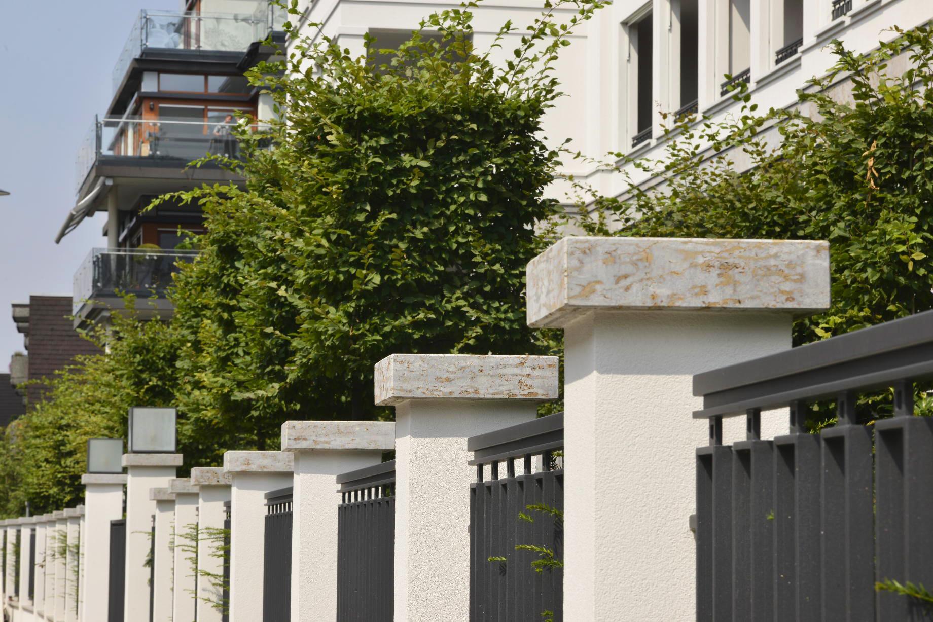 Abdeckplatten aus grauem Mooser Muschelkalk von TRACO an einem Zaunsystem in Düsseldorf