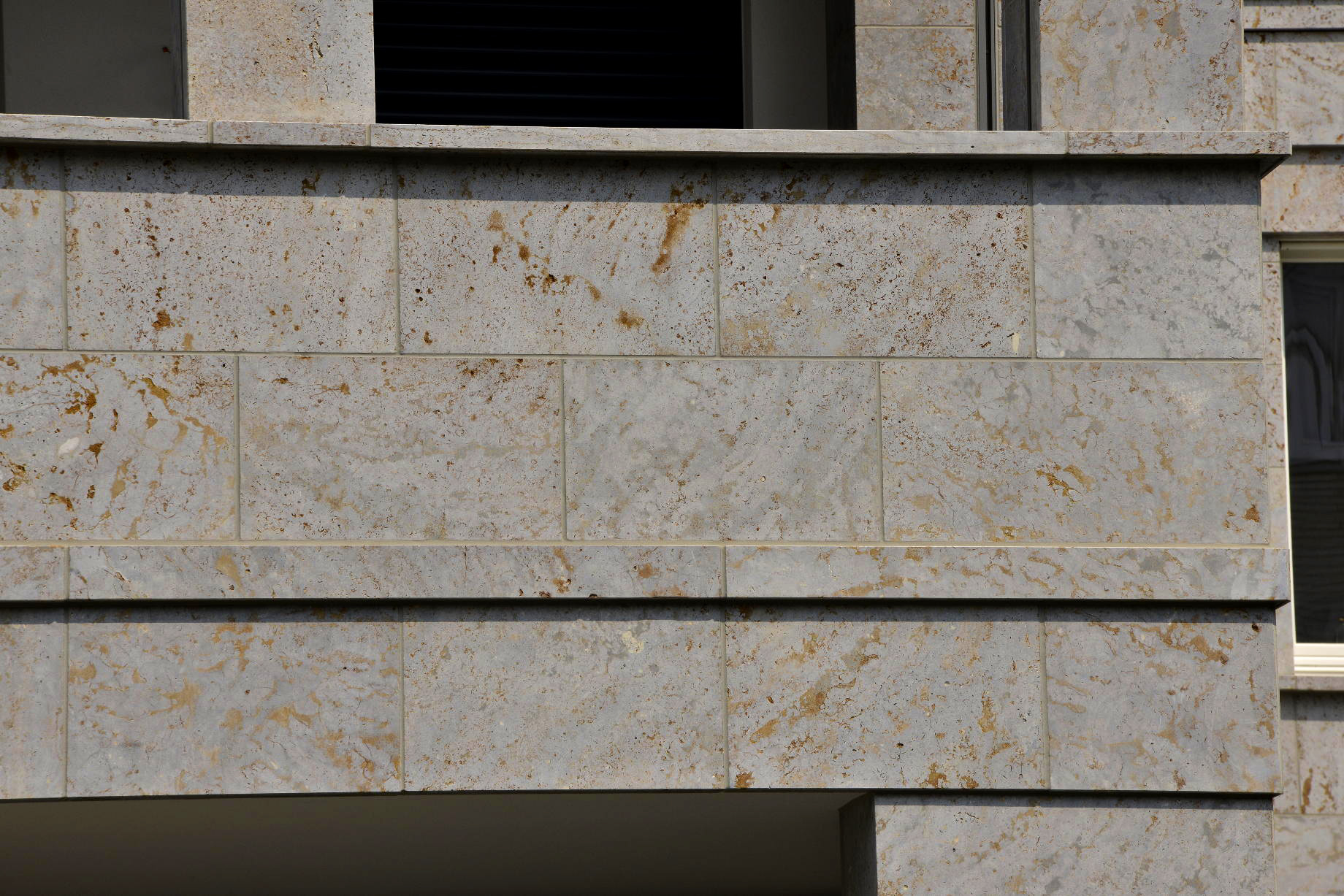 Detailansicht von Fassadenplatten aus grauem Mooser Muschelkalk von TRACO an einer Luxuswohnanlage in Düsseldorf