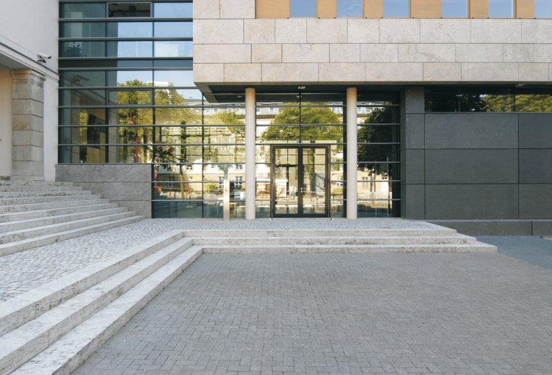 TRACO Fassade aus Travertin und Blockstufen und Pflaster aus Muschelkalk