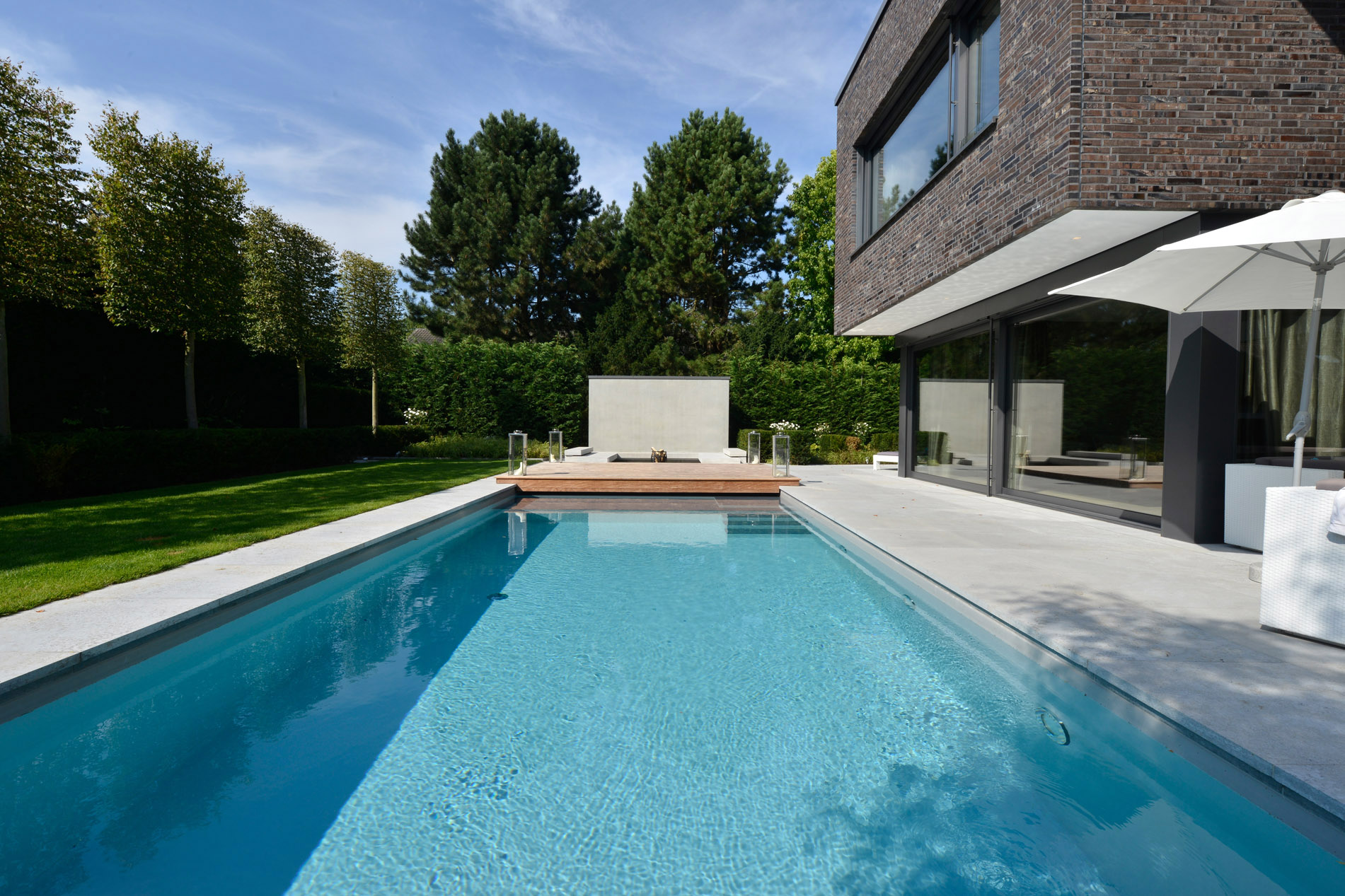 Villa mit Naturstein Bodenplatten und Poolumrandung aus Kohlplatter Muschelkalk edelgrau von TRACO