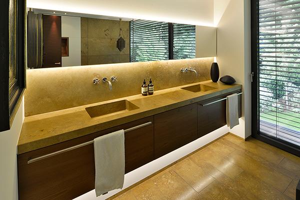 massiver Waschtisch, Wandverkleidung und Bodenplatten aus Travertin Naturstein von TRACO