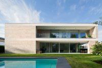 Villa mit einer massiven Natursteinfassade aus Bauhaus Travertin von TRACO