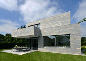 Villa mit einer Naturstein Fassade und Terrassenplatten aus Muschelkalk edelgrau